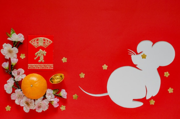 Dekoracja festiwalu chińskiego nowego roku na czerwono, która wycięta w kształcie szczura nałożona na białym papierze. znak na sztabce oznacza, na czerwonym pakiecie pieniędzy oznacza wielkie życzenie. Premium Zdjęcia