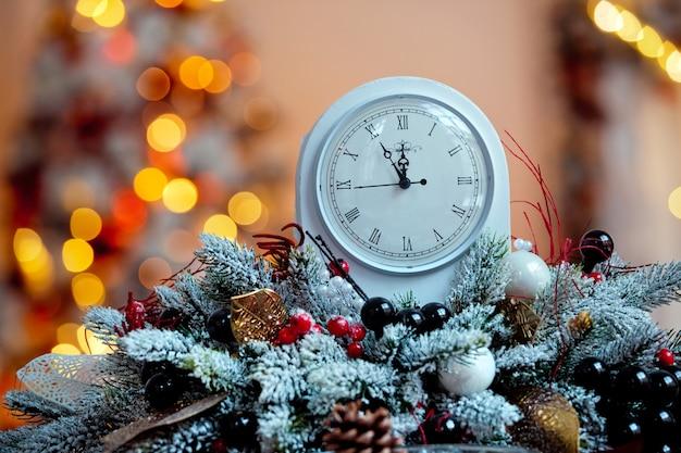 Dekorację świąteczną We Wnętrzu Pokoju. Zegary Na Stole Z Nieostre Tło, Efekt Bokeh Premium Zdjęcia