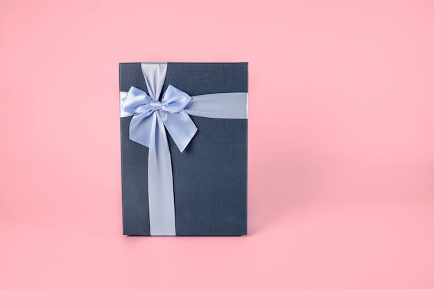 Dekoracyjne Ciemnoniebieskie Pudełko Z Jasnoniebieską Kokardą Na Różowym Pastelowym Tle, Zapakowane Pudełko Z Wycinek ścieżki Premium Zdjęcia