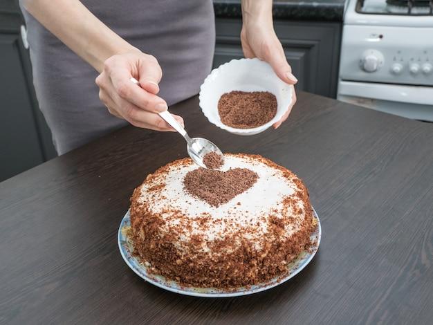 Dekorowanie Ciasta Na Walentynki. Ręcznie Robione Ciasto Z Polewą Z Twarogu I Czekoladowym Sercem. Premium Zdjęcia