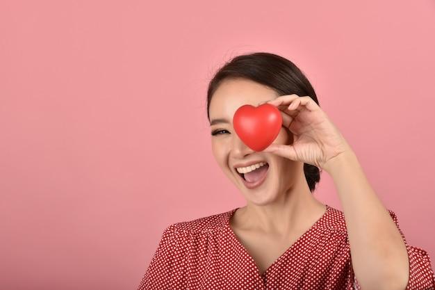 Delikatna Azjatykcia Kobieta Trzyma Czerwonego Serce, Szczęśliwa Uśmiechnięta Kobieta Pokazuje Miłość Znaka Wspierać I Zachęcać, Sprawdzać Zdrowie Serca. Premium Zdjęcia