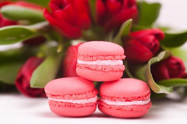 Delikatne czerwone tulipany i macarons na drewnianych. zbliżenie. kompozycja kwiatów kwiatowa wiosna. walentynki, wielkanoc, dzień matki. Premium Zdjęcia
