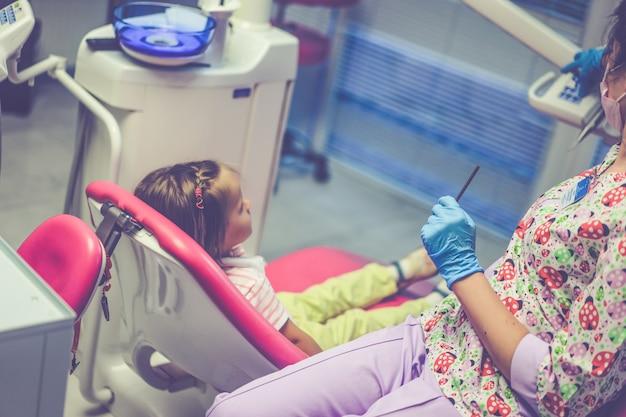 Dentysta dziecięcy. mała dziewczynka przy przyjęciem przy dentystą. Darmowe Zdjęcia