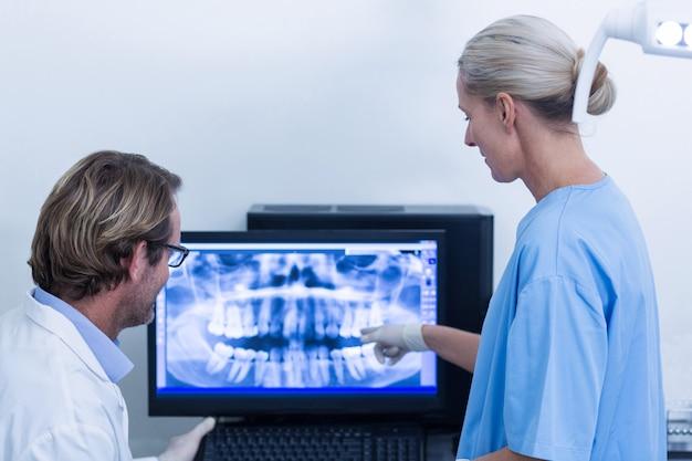 Dentysta I Asystent Dentystyczny Omawiając Zdjęcie Rentgenowskie Na Monitorze Premium Zdjęcia