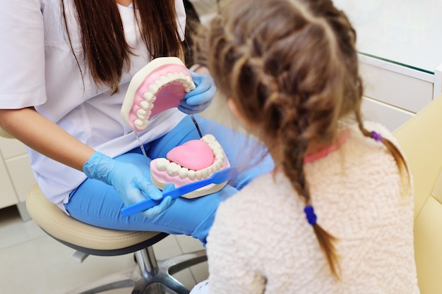 Dentysta mówi dziecku o higienie jamy ustnej Premium Zdjęcia