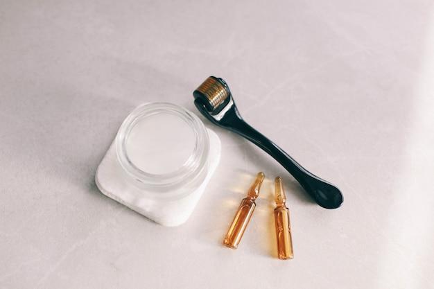 Dermaroller i serum obok kremu przeciwzmarszczkowego Premium Zdjęcia