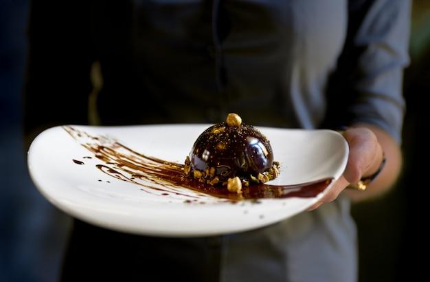Deser Francuskiego Mini Musu W Polewie Czekoladowej Na Talerzu, Deser W Rękach Kelnerki. Premium Zdjęcia
