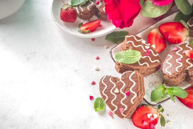 Deser Walentynki. Czekoladowe Mini Ciastka Biszkoptowe W Kształcie Serca Z Truskawkami I Miętą. Widok Z Góry Premium Zdjęcia