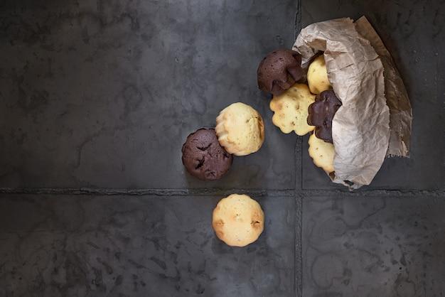 Deserowe, Mleczne I Czekoladowe Babeczki W Papierowej Torbie. Na Szarym Tle Betonu Premium Zdjęcia
