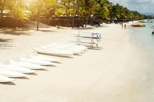 Deski Surfingowe Na Plaży Z Rzędu Gotowe Dla Surferów. Tropikalny Słoneczny Dzień Na Mauritiusie. Premium Zdjęcia