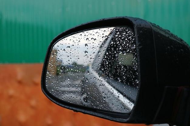 Deszcz Spada Na Lusterko Boczne Samochodu W Deszczowy Dzień. Premium Zdjęcia