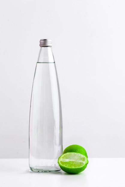Detox natchnąca woda z wapnem w szklanej butelce na białym tle Premium Zdjęcia