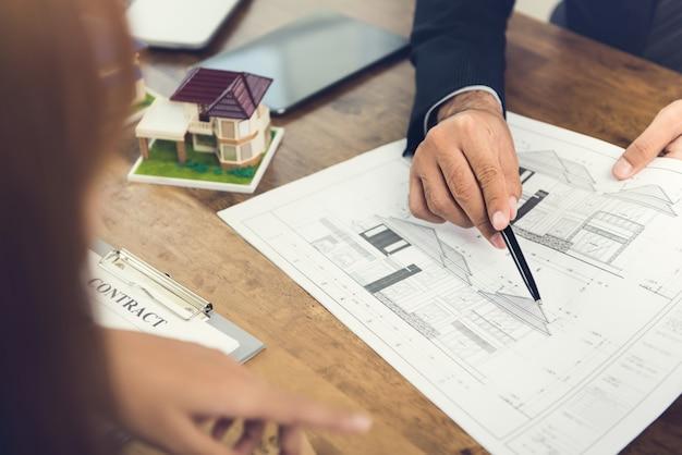 Deweloper wyjaśniający koncepcję mieszkaniową kobiecie biznesu na potrzeby deweloperskie Premium Zdjęcia
