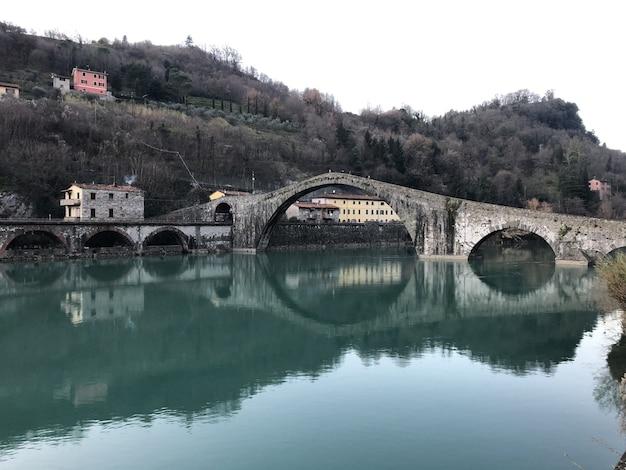 Diabelski Most Otoczony Wzgórzami Porośniętymi Lasami Odbijającymi Się W Jeziorze W Borgo A Mozzano Darmowe Zdjęcia