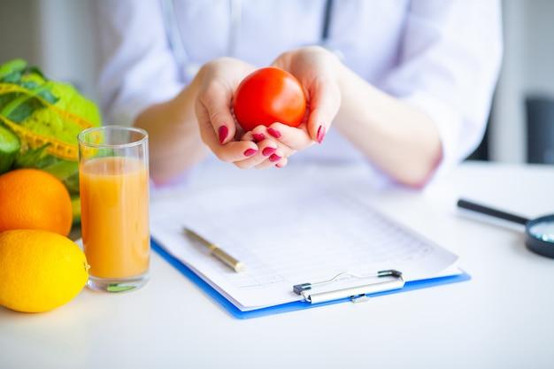 Dieta. doktor dietetyka trzymać pomidora. pojęcie naturalnego jedzenia i zdrowego stylu życia. koncepcja diety fitness i zdrowej żywności. zbilansowana dieta z warzywami. Premium Zdjęcia
