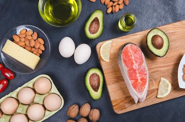 Dieta Ketonowa, Zdrowa żywność O Niskiej Zawartości Węglowodanów. Awokado, Ryby, Olej, Orzechy Na Czarnym Tle Premium Zdjęcia