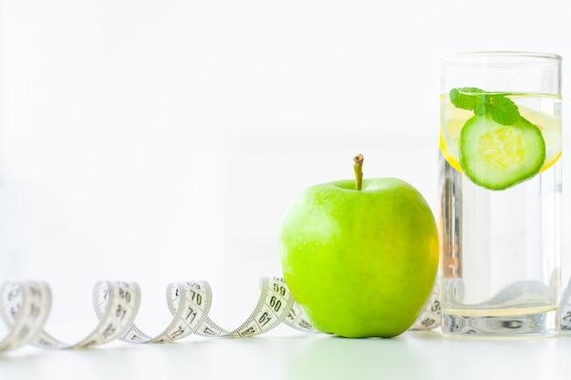 Dieta. koncepcja diety fitness i zdrowej żywności. zbilansowana dieta z owocami. świeże owoce i szklana woda, taśma miernicza Premium Zdjęcia