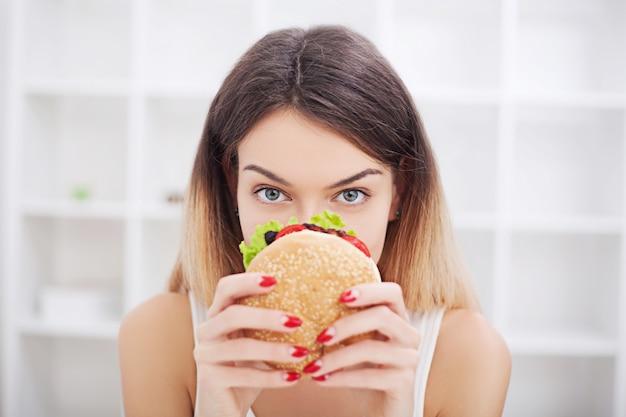 Dieta. Młoda Kobieta Z Taśmą Klejącą Na Ustach, Uniemożliwiając Jej Jedzenie Fast Foodów. Zdrowe Odżywianie Premium Zdjęcia