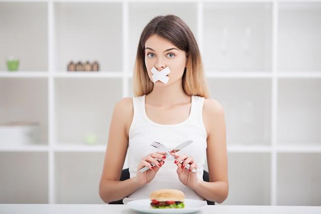 Dieta. Młoda Kobieta Z Taśmą Klejącą Na Ustach, Zapobiegając Jej Jeść Fast Foodów. Premium Zdjęcia