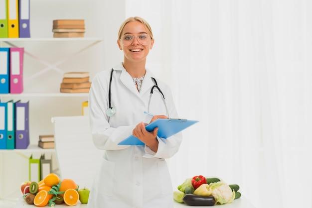 Dietetyk smiley o średnim ujęciu z stetoskopem Darmowe Zdjęcia