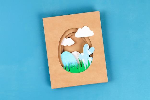 Diy Kartki Wielkanocne Z Papieru. Tom Kartki Z Królika, Jajko Na Niebieskim Tle. 3d. Premium Zdjęcia