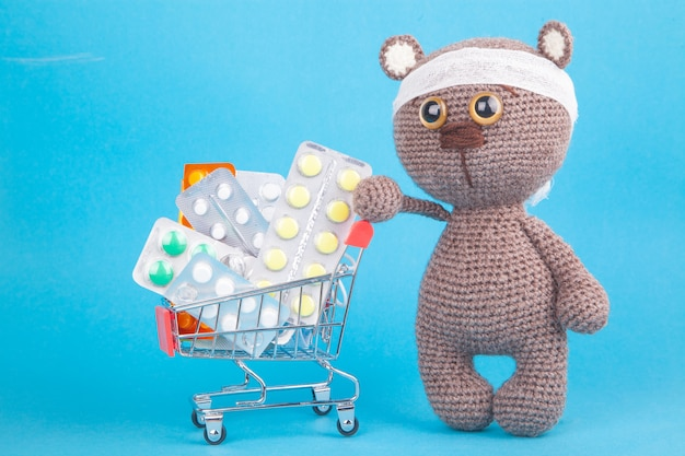 Diy zabawka. dzianiny brązowy niedźwiadek. zakupy leków, koszty opieki zdrowotnej i leki na receptę za pomocą wózka na zakupy wypełnionego pigułkami Premium Zdjęcia