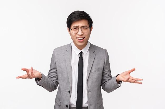 Dlaczego Chcesz Portret W Pasie Zaniepokojony I Sfrustrowany Młody Mężczyzna Azji W Szarym Kolorze Premium Zdjęcia
