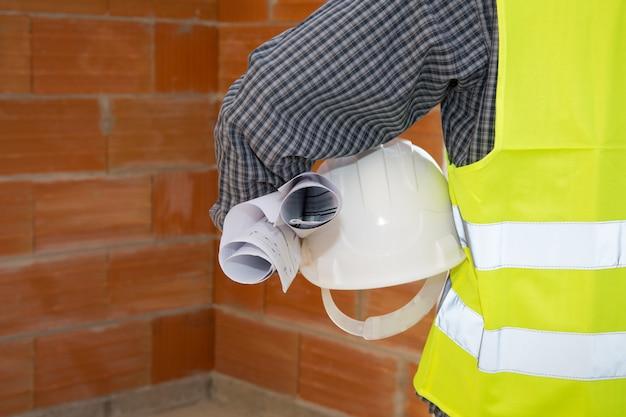 Dłoń Trzymająca Kask Przed Betonową ścianą Premium Zdjęcia