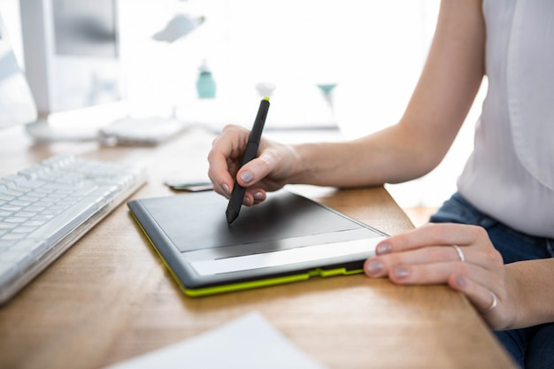 Dłoń trzymająca pióro, które szkicuje na cyfrowym tablecie rysunkowym Premium Zdjęcia