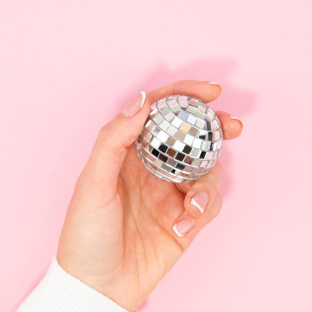 Dłoń trzymająca srebrna kula disco Darmowe Zdjęcia