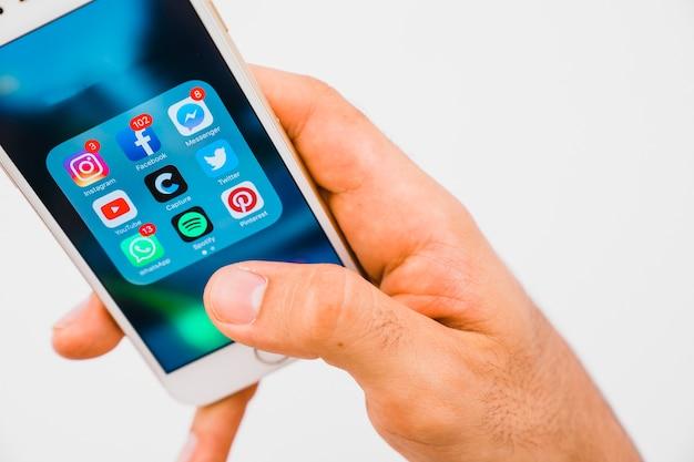 Dłoń Trzymająca Telefon Z Aplikacjami Premium Zdjęcia