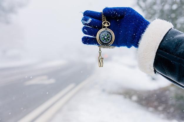 Dłoń Trzymająca Złoty Kompas Na Drodze śnieżny Krajobraz. Premium Zdjęcia