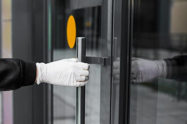 Dłoń W Rękawiczce Otwiera Drzwi Na Ulicy. Mężczyzna W Rękawiczkach Trzyma Klamkę Premium Zdjęcia