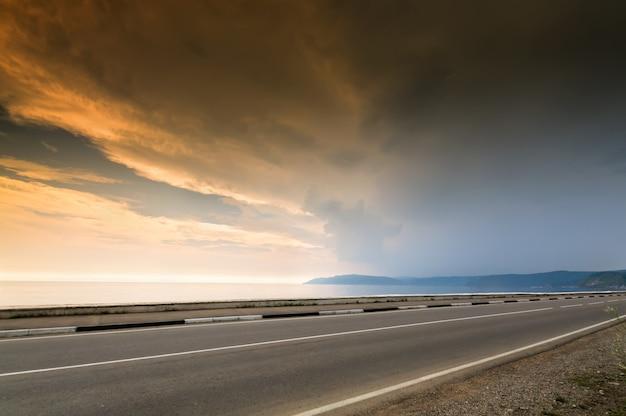 Długa droga i linia morska, jezioro lub ocean w czasie zachodu słońca z pochmurnego nieba Premium Zdjęcia