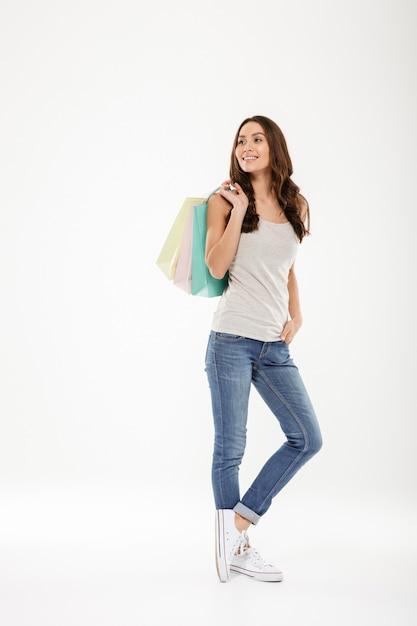Długa Galanteryjna Kobieta Patrzeje Daleko Od I Trzyma Kolorowych Torba Na Zakupy, Odizolowywających Nad Bielem Darmowe Zdjęcia