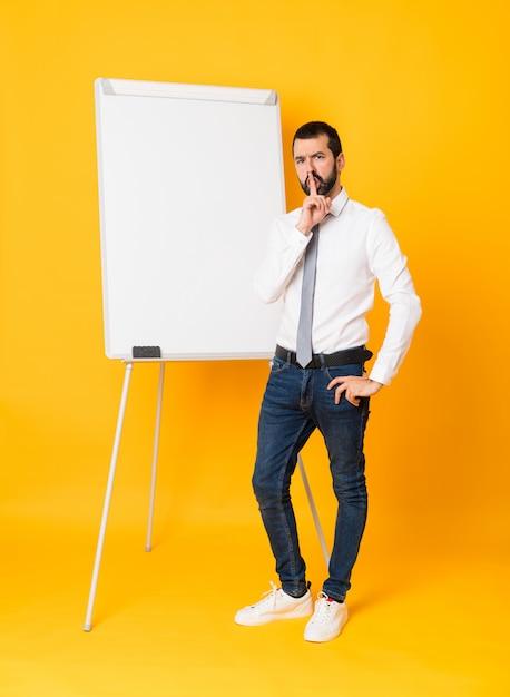 Długi strzał daje prezentaci na białej desce biznesmen nad odosobnionym kolorem żółtym pokazuje znak cisza gesta kładzenia palec w usta Premium Zdjęcia