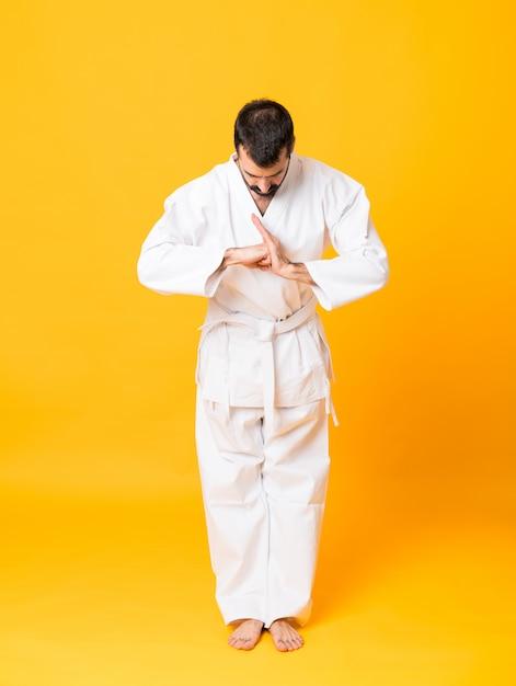 Długi strzał mandoing karate nad odosobnionym kolorem żółtym Premium Zdjęcia