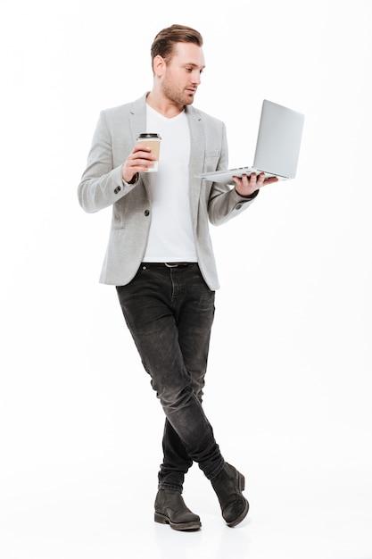Długi Wizerunek Młody Przedsiębiorca W Kurtki Pozyci Z Srebnym Laptopem I Wynos Kawą W Rękach, Odizolowywający Nad Biel ścianą Darmowe Zdjęcia