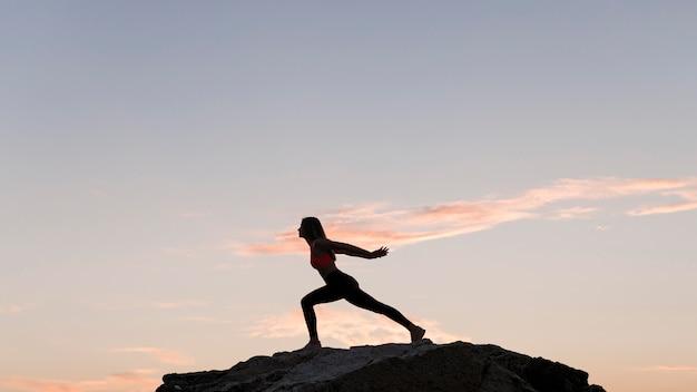Długie Strzał Kobiety Stojącej W Pozycji Sportowej Na Skale Z Miejsca Na Kopię Darmowe Zdjęcia