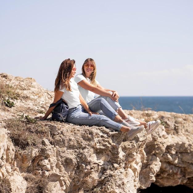 Długie Ujęcia Przyjaciół Siedzących Na Skałach Nad Oceanem Darmowe Zdjęcia