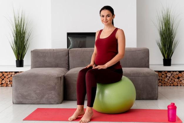 Długie Ujęcie Kobieta W Ciąży Siedzi Na Piłce Fitness Premium Zdjęcia