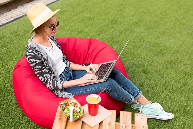 Długie ujęcie kobiety pracującej na jej laptopie Darmowe Zdjęcia