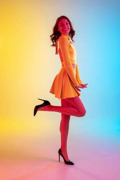 Długie Włosy. Piękna Uwodzicielska Dziewczyna W Modnej Sukience Na żółto-niebieskim Tle Gradientu W świetle Neonu. Darmowe Zdjęcia
