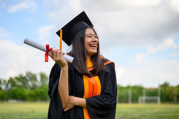 Długowłose studentki w czarnych sukienkach z falbanami wyrażające radość z ukończenia studiów. Premium Zdjęcia