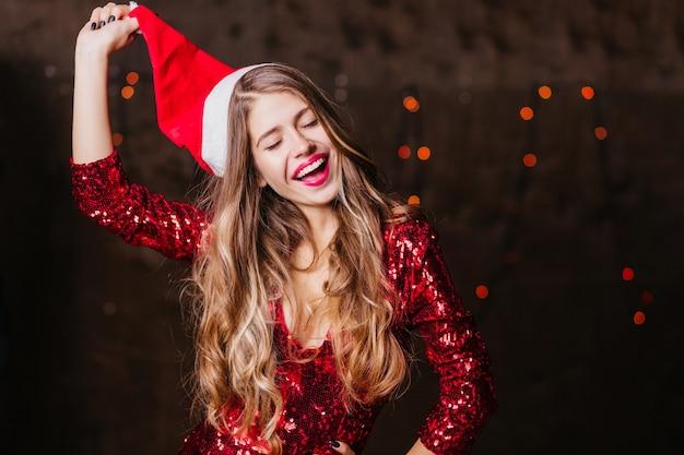 Długowłosy Brunetka Kobieta Zdejmując Czapkę świętego Mikołaja Darmowe Zdjęcia