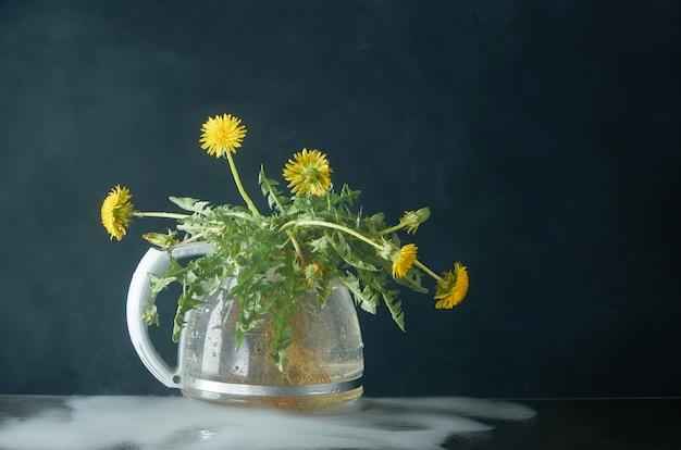 Dmuchawiec z korzeniami i liśćmi w szklanym czajniku na ciemności w dymie Premium Zdjęcia