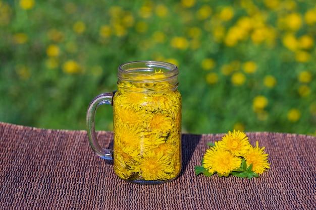 Dmuchawiec żółty Kwiat Herbata Napój W Szklanym Kubku Na Stole W Tle Przyrody, Na Zewnątrz, Z Bliska. Pojęcie Zdrowego Odżywiania Premium Zdjęcia