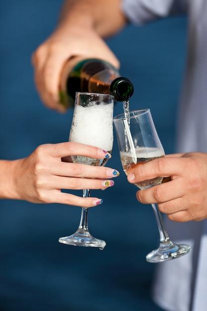 Do kieliszka wlał szampana Premium Zdjęcia