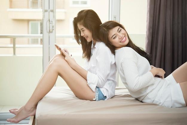 Dobiera się młode azjatykcie kobiety używa smartphone na łóżku z szczęściem. Premium Zdjęcia
