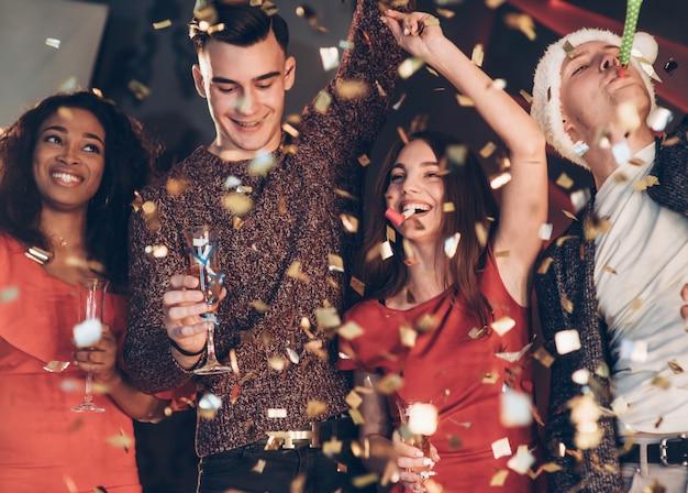 Dobry Humor. Powietrze W Konfetti. Czterech Dobrych Przyjaciół W Dobrych Ubraniach Jest Na Imprezie Nowego Roku Premium Zdjęcia